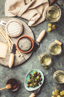 Białe wino z asortymentem wędlin na kamiennym tle