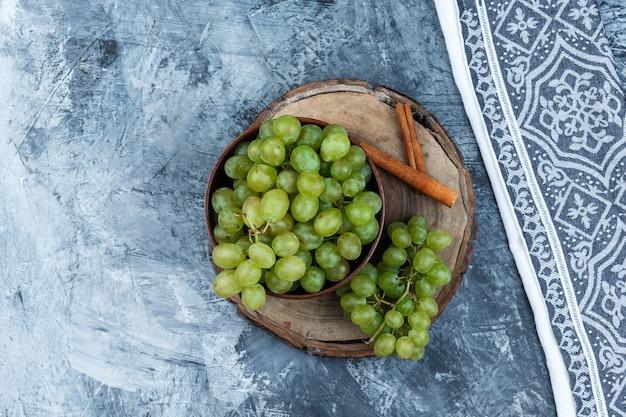 Białe winogrona, cynamon na drewnianej desce z widokiem z góry na ręcznik kuchenny na granatowym tle marmuru