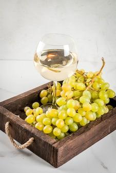 Białe winogrona i białe wino w szklance, w drewnianej tacy na białym marmurowym stole. skopiuj miejsce