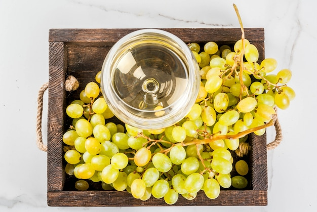 Białe winogrona i białe wino w szklance, w drewnianej tacy na białym marmurowym stole. skopiuj widok z góry