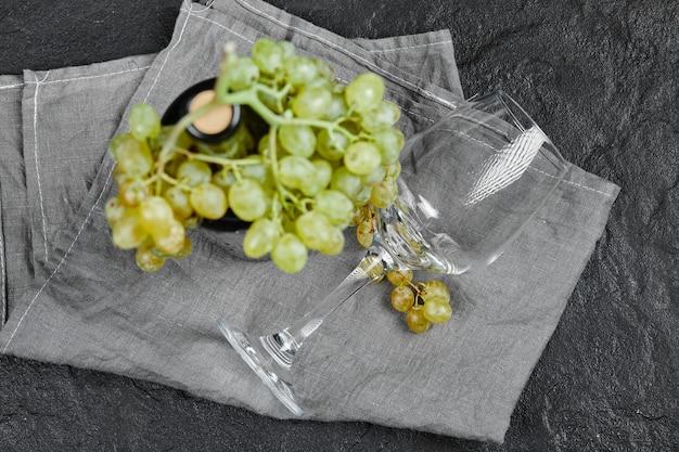 Białe winogrona i butelka wina na ciemnej powierzchni