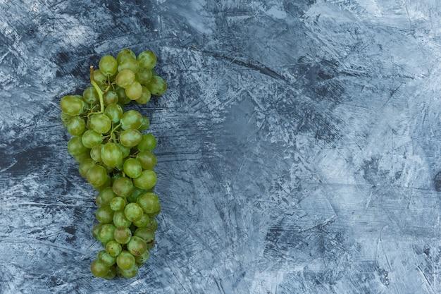 Białe winogrona leżały płasko na ciemnoniebieskim tle marmuru. poziomy
