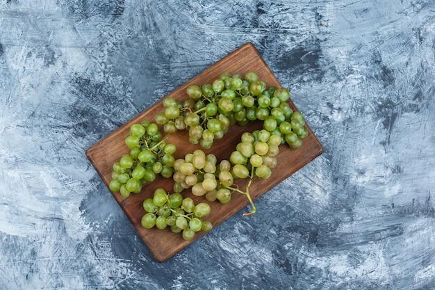 Białe winogrona leżały płasko na desce do krojenia na ciemnoniebieskim tle marmuru. poziomy