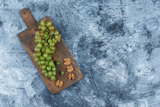 Białe winogrona, orzechy włoskie na desce do krojenia na ciemnoniebieskim tle marmuru. wolne miejsce w poziomie na tekst
