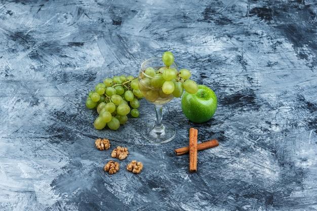 Białe winogrona, zielone jabłko z cynamonem, orzechy włoskie, szklanka whisky z dużym kątem widzenia na granatowym marmurowym tle