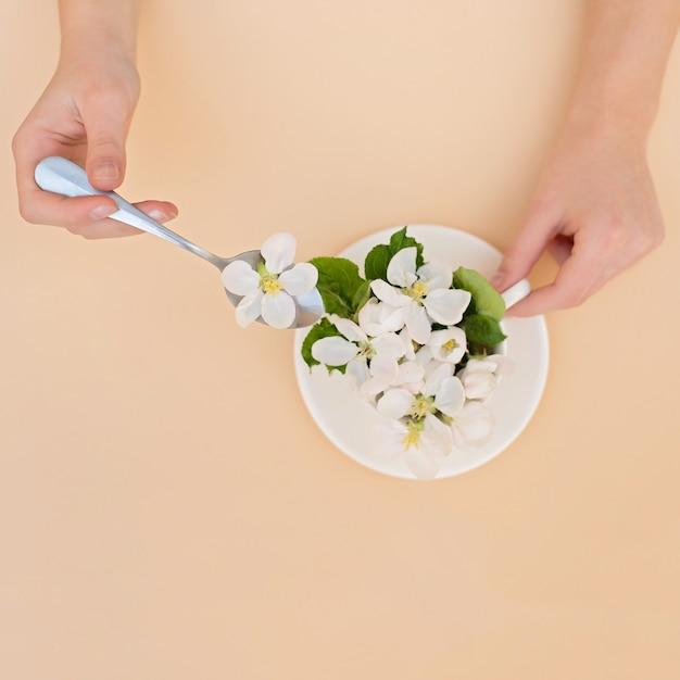 Białe wiosenne jabłko kwitnących kwiatów w filiżance kawy z łyżką w ręce na beżowym tle. koncepcja wiosna lato. kartka z życzeniami. skopiuj miejsce leżał płasko.