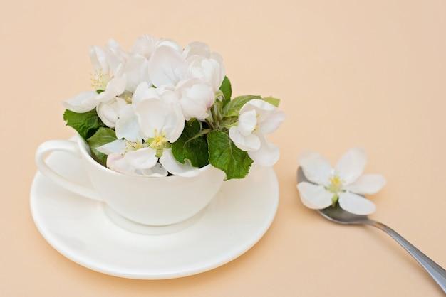 Białe wiosenne jabłko kwitnie kwitnące kwiaty w filiżance kawy z łyżeczką na beżowym tle. koncepcja wiosna lato. kartka z życzeniami.