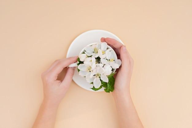 Białe wiosenne jabłonie kwitnące kwiaty w filiżance kawy w żeńskich eleganckich rękach na beżowym tle. koncepcja wiosna lato. leżał płasko.