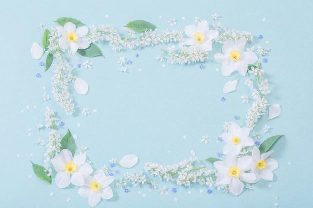 Białe wiosenne kwiaty na niebieskiej ścianie