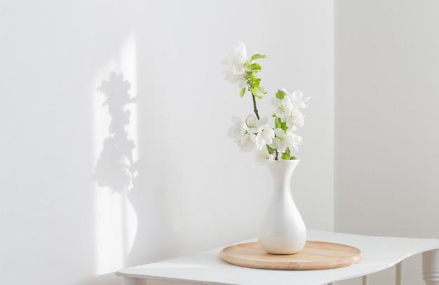 Białe wiosenne kwiaty w wazonie na półce vintage