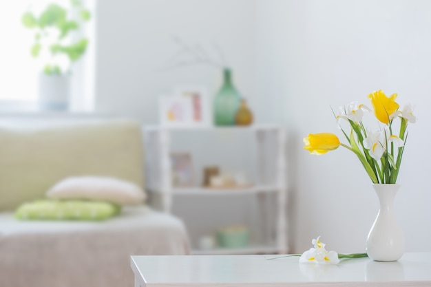 Białe wnętrze domu z wiosennymi kwiatami i dekoracjami