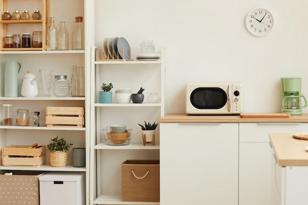 Białe wnętrze kuchni z minimalistycznym wystrojem i drewnianym wystrojem