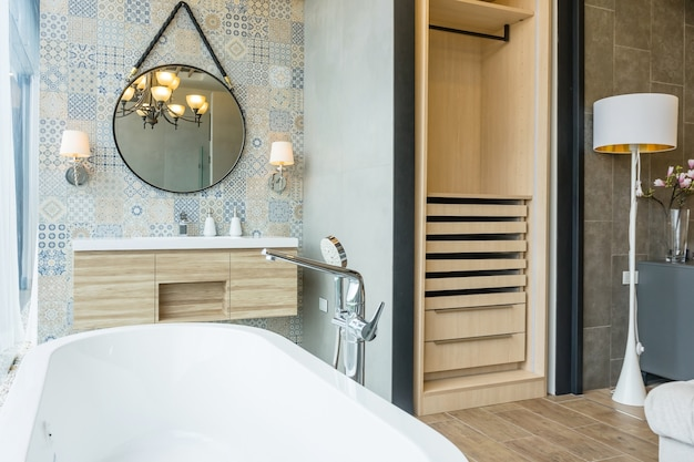 Białe wnętrze łazienki z mozaiką, biało-drewniana podłoga, owalna wanna, umywalka i okrągłe lustra