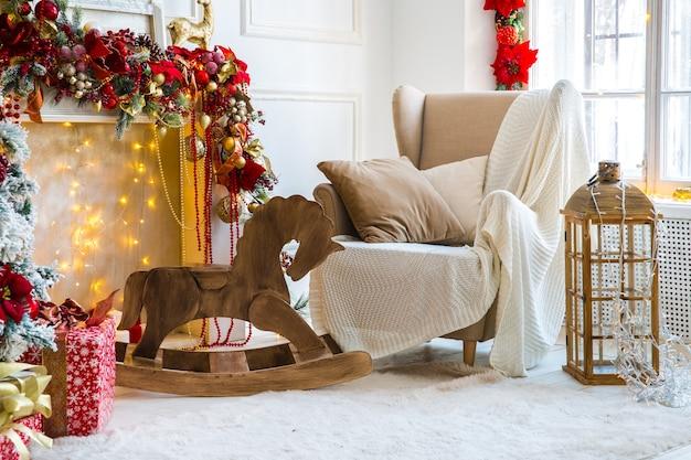 Białe wnętrze pokoju w odcieniach czerwieni z dekorowanym drzewem noworocznym, obecnymi pudełkami i sztucznym kominkiem