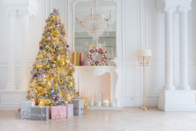 Białe wnętrze pokoju z noworocznym drzewkiem, obecne pudełka i sztuczny kominek