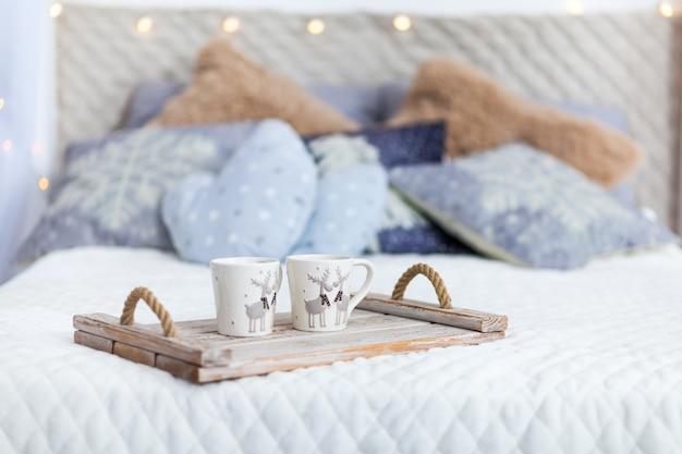 Białe wygodne łóżko i lampki choinkowe