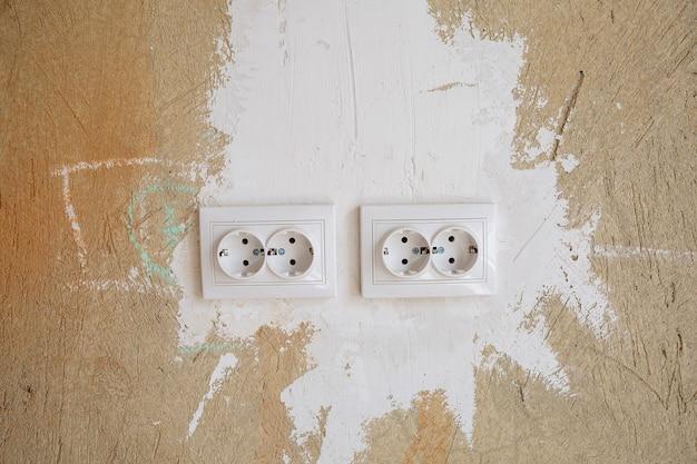 Białe wyloty na betonowej ścianie podczas naprawy. montaż kielichów podczas remontu w świeżych pustych ścianach cementowych