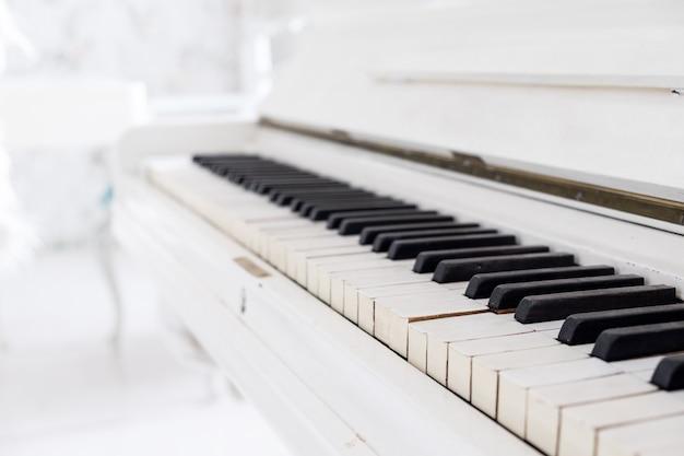 Białe zabytkowe pianino w białym pokoju