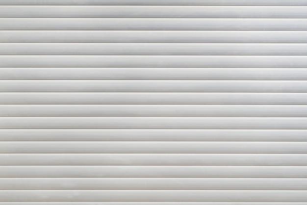 Białe żaluzje z zamkiem w oknie. rolety w tle.