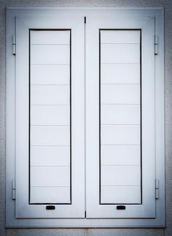 Białe zamknięte okiennice w oknach na białej ścianie. ścieśniać