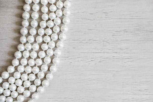 Białe żeńskie koraliki na białym drewnianym tle, żeńska biżuteria na białym drewnianym stole