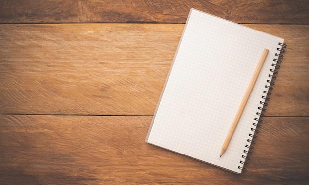 Białe zeszyty i ołówek leżący na drewnianym stole