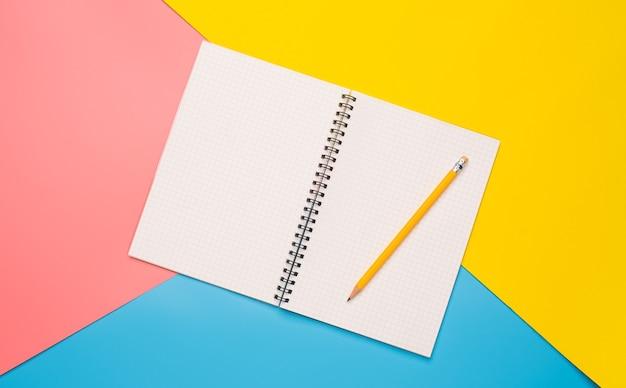 Białe zeszyty i ołówek nałożony na kolor