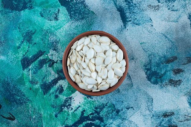 Białe ziarna w misce, na marmurowym stole.
