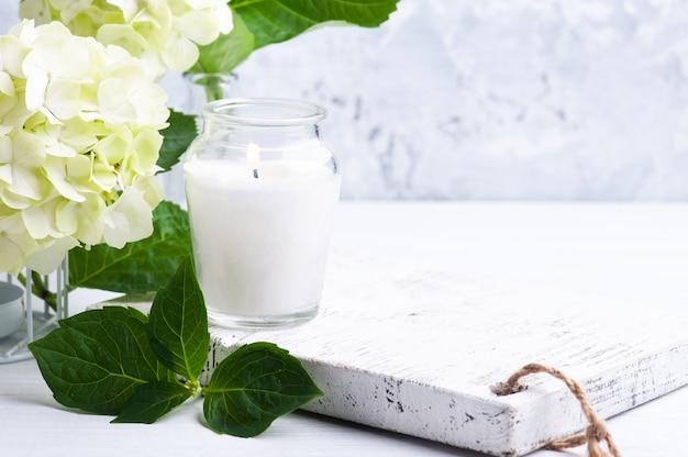 Białe, zielone kwiaty hortensji w doniczce i zapalona świeca na betonie