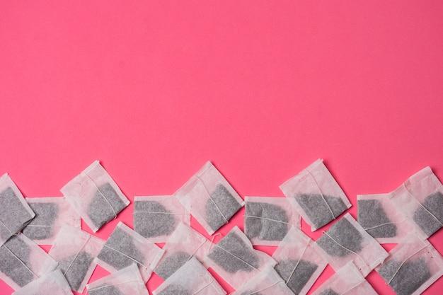 Białe ziołowe herbaty torby na różowym tle