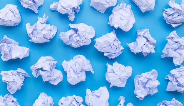 Białe zmięte papierowe piłki na błękitnym tle.
