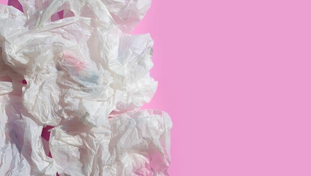 Białe zmięte plastikowe torby na różowej powierzchni