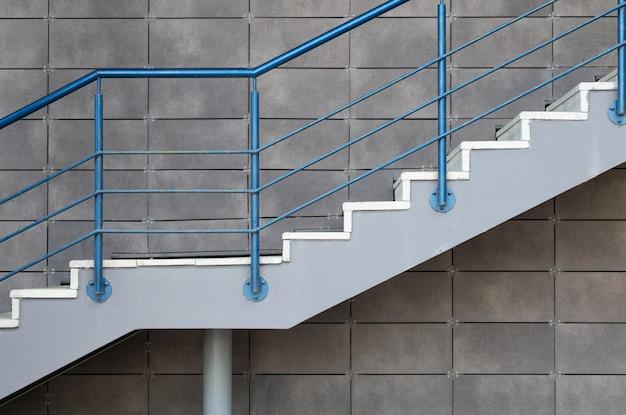 Białego cementu schodki z błękitną stalową poręczą na popielatym kafelkowym ściennym tle
