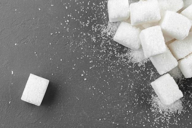 Białego cukieru sześciany nad czarnym tła zakończeniem up