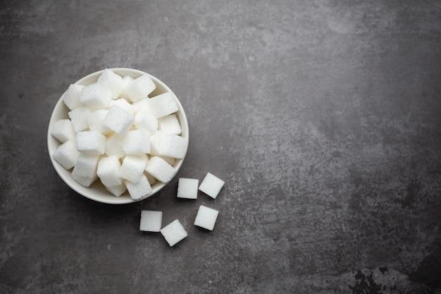 Białego cukieru sześciany w pucharze na stole.