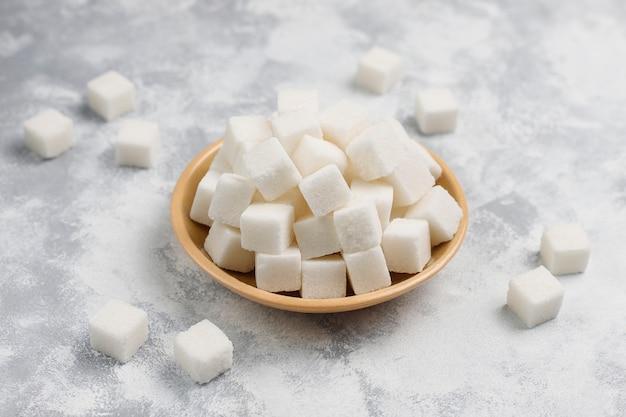 Białego cukru sześciany na betonie, odgórny widok