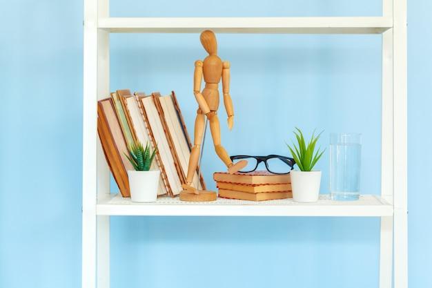 Białego metalu stojak z książkami przeciw błękitnemu tłu