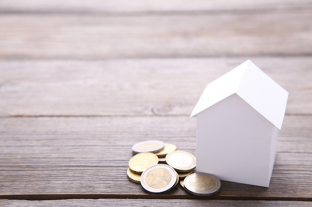 Białego papieru dom z monetami na szarym tle