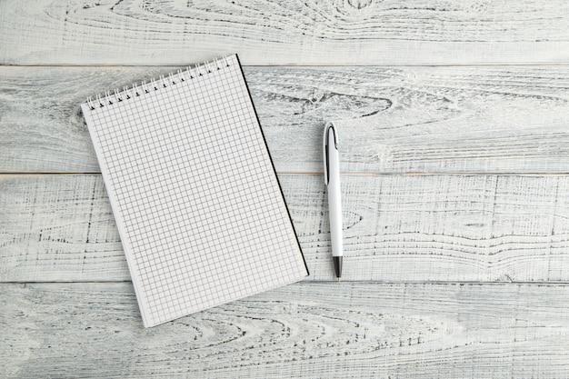 Białego papieru notatnik i biały długopis na tle brudny