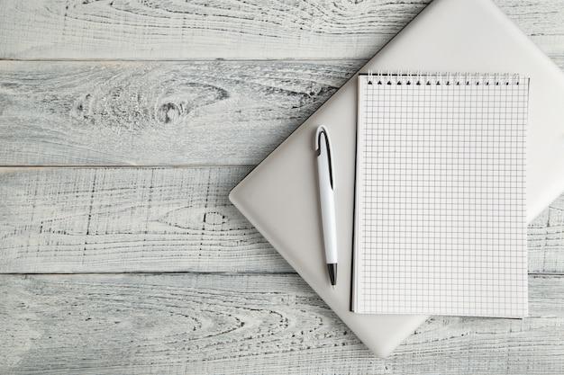 Białego papieru notatnik i laptop na rocznika podławym białym drewnianym tle. widok z góry. leżał płasko