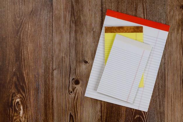 Białego papieru notepad na projekta mieszkaniu kłaść na drewnianym tle