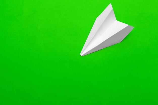 Białego papieru samolot na zielonego papieru tle