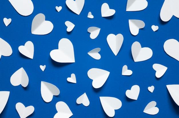 Białego papieru serca na niebieskim tle, widok z góry. kolor roku 2020 classic blue.