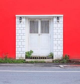 Białego rocznika retro drewniany drzwi na czerwieni ściany tle. koncepcja architektury wnętrz domu