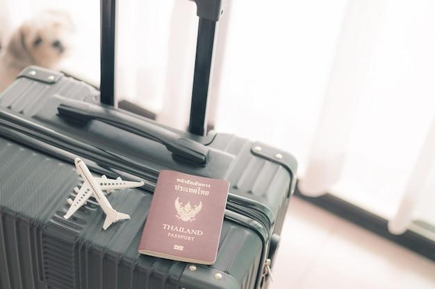 Białego samolotu model i tajlandzki paszport na czarnym bagażu przeciw zamazanemu cutely psu dla pojęcia podróży i podróży