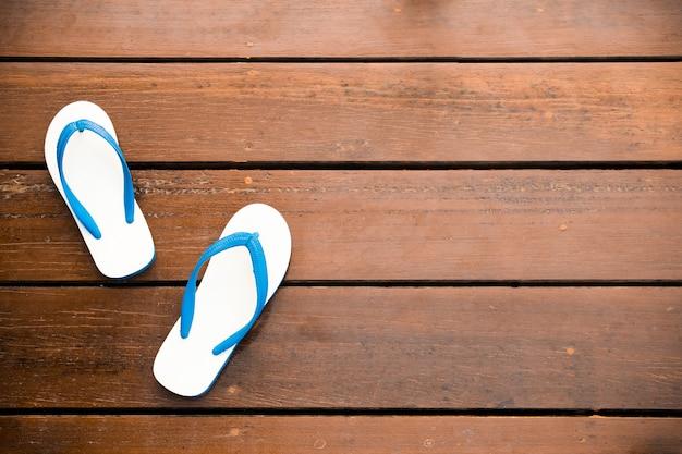 Biali flipflops na drewnianym tle - rocznika styl