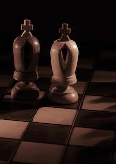 Biali i czarni królowie na szachownicy