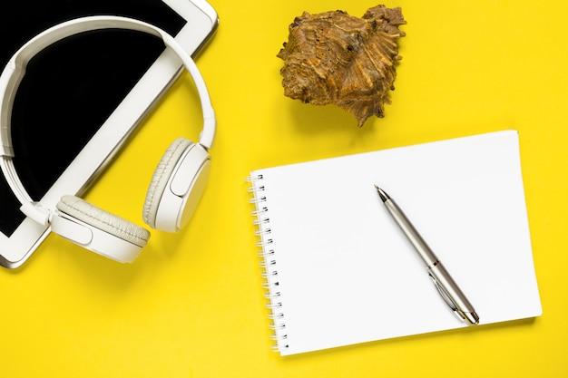 Biali nowożytni słuchawki i pastylka na trendować żółtego backgound mieszkanie odnosić się odgórnego widoku tekst dla teksta