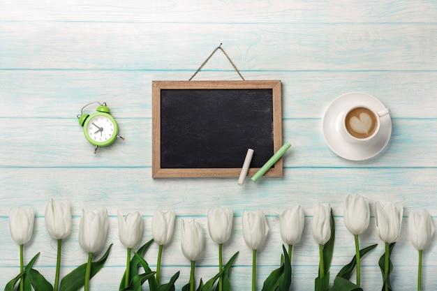 Biali tulipany z kredową deską, filiżanką kawy i budzikiem na błękitnych drewnianych deskach. dzień matki