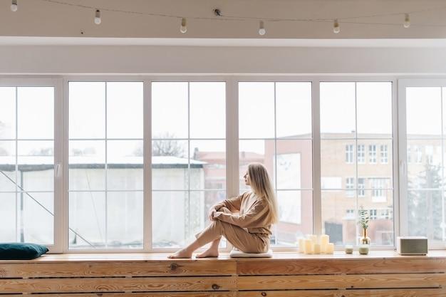 Biało-beżowe przytulne wnętrze z dużym oknem i piękna dziewczyna w stylowym beżowym garniturze siedzącym przy oknie.